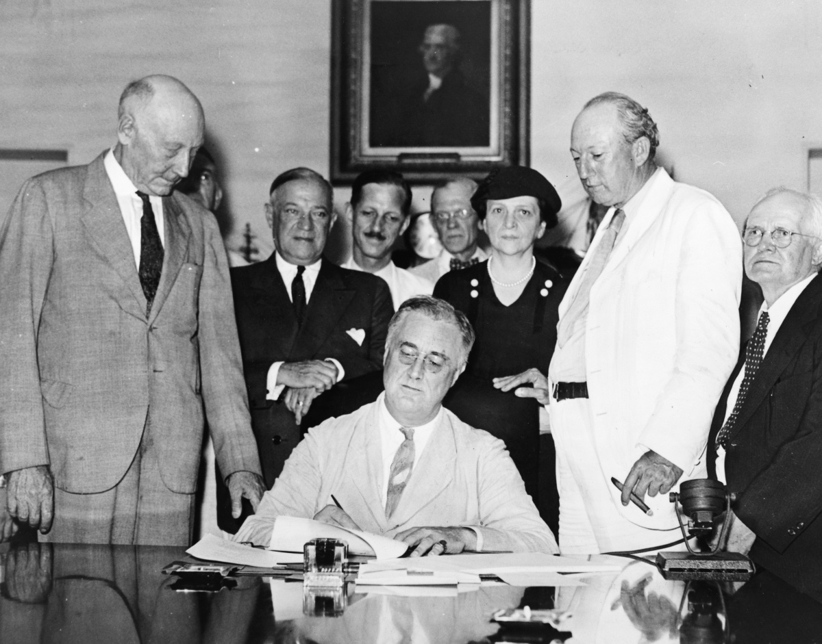President Franklin D. Roosevelt signs the Social Security Act of 1935 into law.